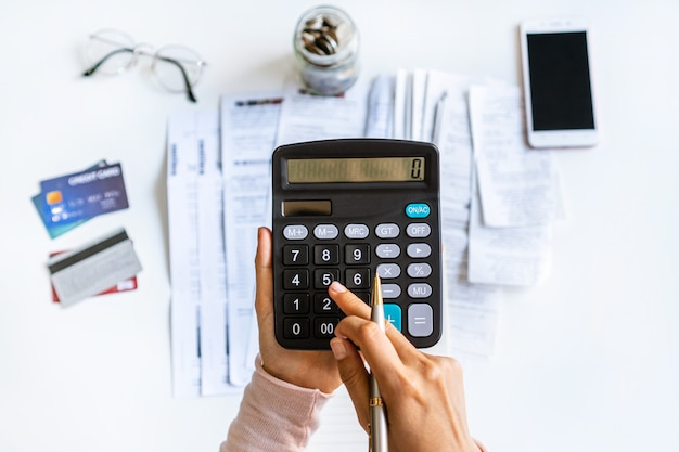 Vista superiore della spesa mensile calcolatrice della donna di affari al suo scrittorio. concetto di risparmio. concetto di pagamento finanziario e rateale.
