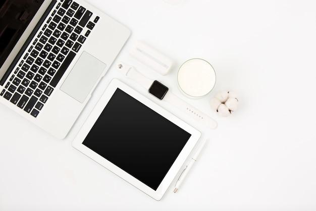 Vista superiore della tavola bianca dell'ufficio con il computer portatile