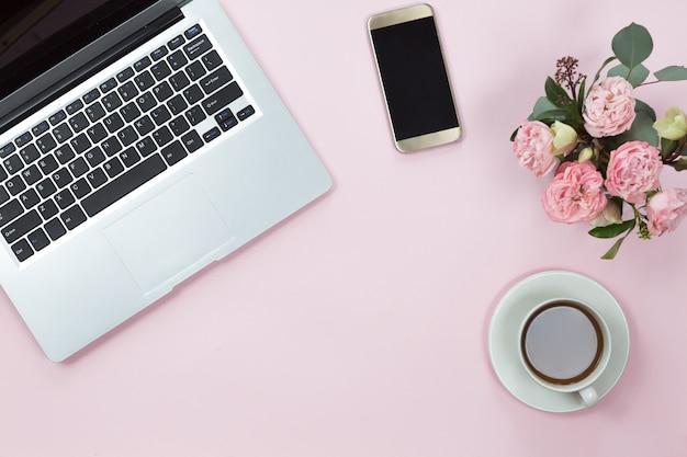 Vista superiore della tavola rosa della scrivania con il computer portatile, lo smartphone, la tazza di caffè e i fiori. copia spazio, disteso.