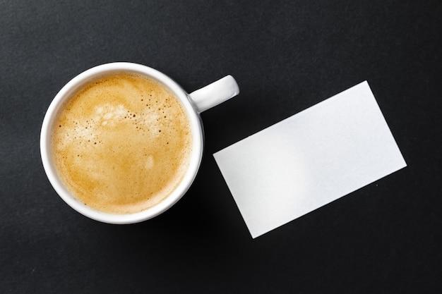Vista superiore della tazza con caffè espresso e modello di biglietto da visita bianco