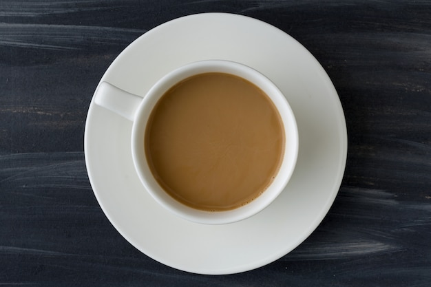Vista superiore della tazza di caffè bianco sul fondo nero della tavola