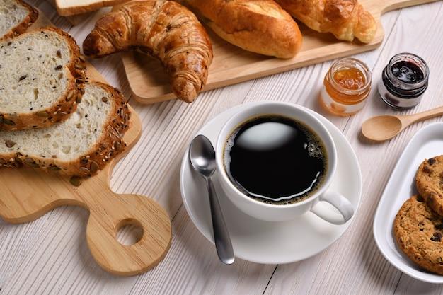 Vista superiore della tazza di caffè con pane o panino, cornetto e forno sulla tavola di legno bianca