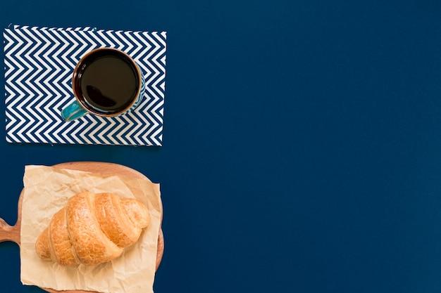 Vista superiore della tazza di caffè nero e croissant su un tagliere e carta artigianale su sfondo blu con spazio di copia. colazione del mattino in stile francese.