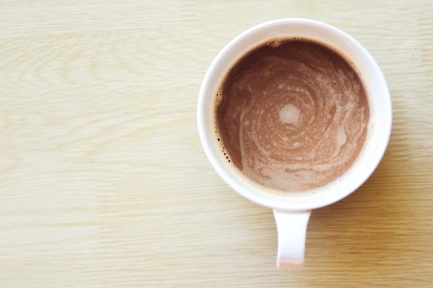 Vista superiore della tazza di caffè sul fondo di legno della tavola.