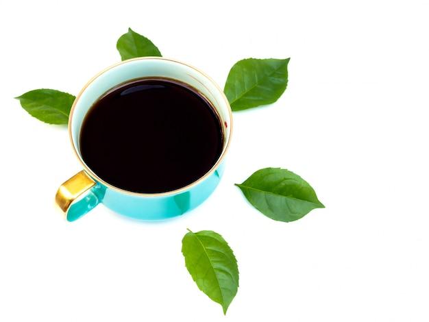 Vista superiore della tazza di ceramica blu con caffè nero e foglie verdi isolate su superficie bianca.