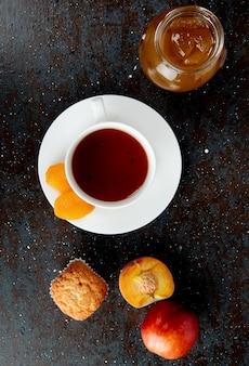 Vista superiore della tazza di tè con l'uva passa sulla bustina di tè e sull'inceppamento della pesca del bigné delle pesche su superficie nera e marrone