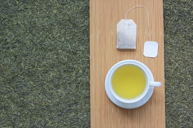 Vista superiore della tazza di tè con la bustina di tè sul fondo secco delle foglie di tè