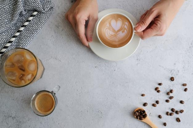 Vista superiore della tazza e dei fagioli di caffè con copyspace. latte piatto per menu, sfondo, banner e pubblicità. preparare una bevanda alla caffeina e uno stile moderno.