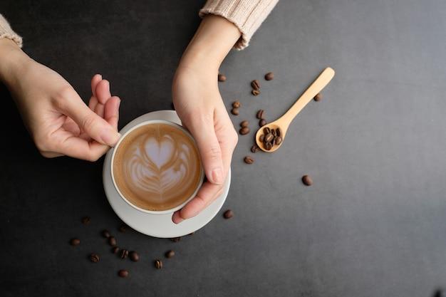Vista superiore della tazza e dei fagioli di caffè con copyspace. preparare una bevanda alla caffeina e uno stile moderno.