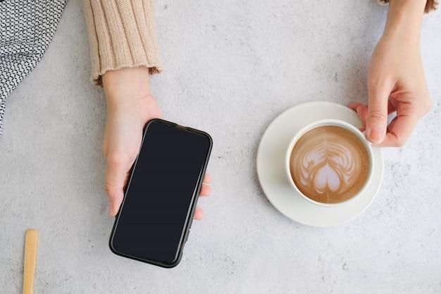 Vista superiore della tazza e del telefono cellulare di caffè con copyspace. latte piatto per menu, sfondo, banner e pubblicità. preparare una bevanda alla caffeina e uno stile moderno.