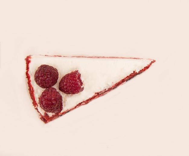 Vista superiore della torta rossa con i lamponi e la crema bianca isolata sopra bianco