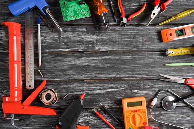 Vista superiore della varietà di strumenti a portata di mano con diversi lavori su fondo di legno nero.