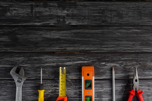 Vista superiore della varietà di strumenti a portata di mano su fondo di legno nero per la festa del lavoro.