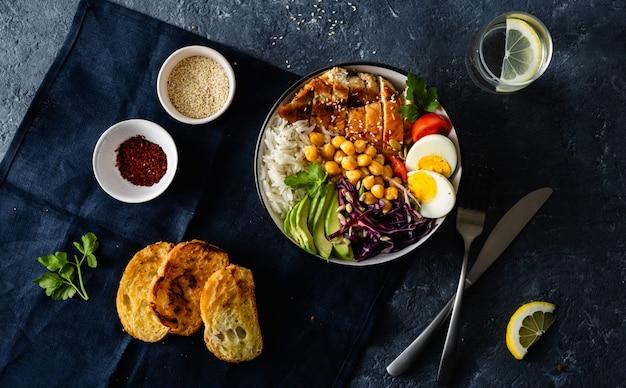 Vista superiore della verdura del petto di pollo dei ceci del riso della ciotola di buddha della tavola di cena