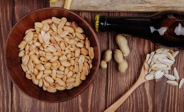 Vista superiore delle arachidi salate dello spuntino in una ciotola di legno con il seme di girasole in un cucchiaio di legno e una bottiglia di birra su rustico