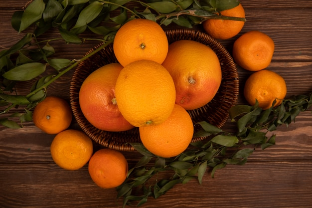 Vista superiore delle arance mature fresche in un canestro di vimini e foglie verdi su legno scuro