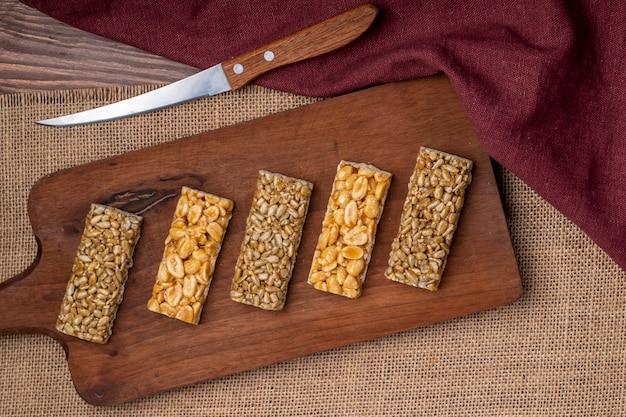 Vista superiore delle barre di miele con i semi di sesamo e di girasole delle arachidi su un bordo di legno su rustico