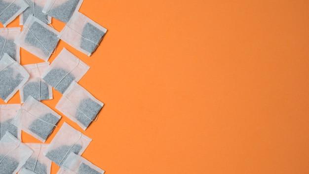 Vista superiore delle bustine di tè bianche su una priorità bassa arancione con spazio per la scrittura del testo