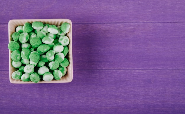 Vista superiore delle caramelle verdi dolci in una ciotola su fondo di legno porpora con lo spazio della copia