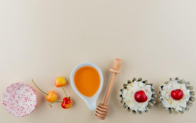 Vista superiore delle ciliege più piovose mature fresche con la ricotta in mini barattoli di crostata e miele con il cucchiaio di legno su bianco con lo spazio della copia