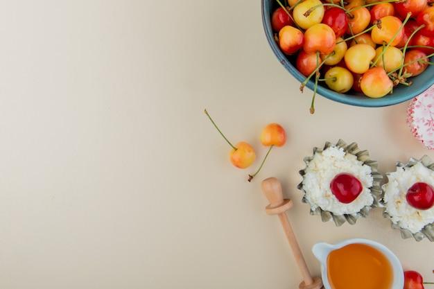 Vista superiore delle ciliege più piovose mature in una ciotola con la ricotta in mini barattoli di latta e miele su bianco con lo spazio della copia