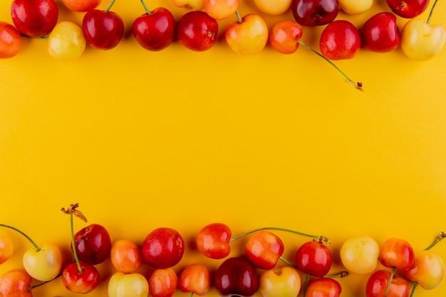 Vista superiore delle ciliege rosse e gialle mature isolate su giallo con lo spazio della copia