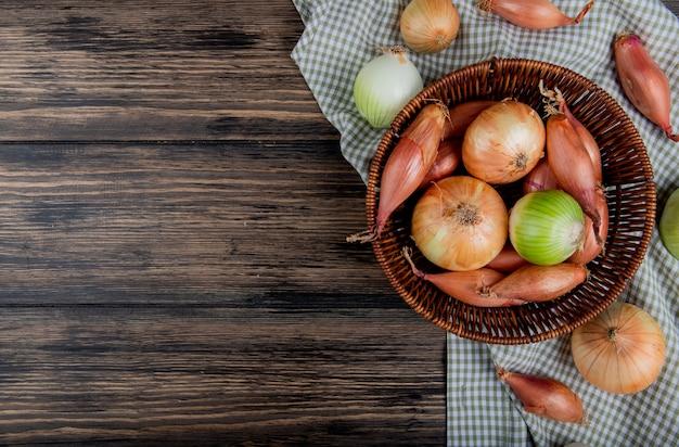 Vista superiore delle cipolle come scalogno dolce e bianco quelle nel cestino sul panno del plaid e sul fondo di legno con lo spazio della copia