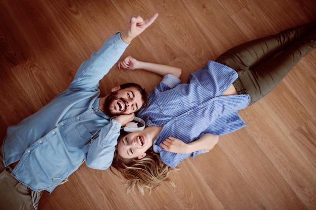 Vista superiore delle coppie caucasiche attraenti che si trovano sul pavimento, ascoltando musica sopra le cuffie e cantando.