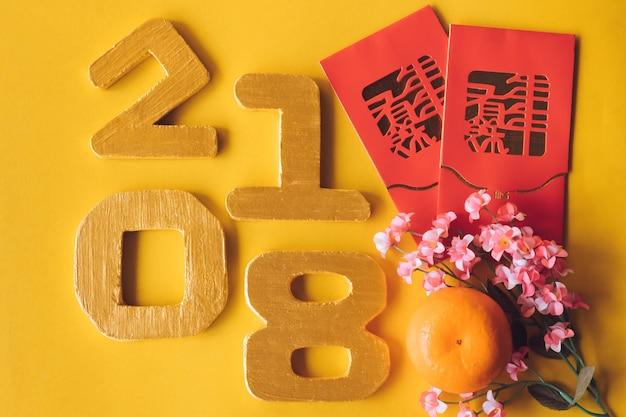 Vista superiore delle decorazioni cinesi di festival del nuovo anno con i numeri 2018 su fondo giallo.