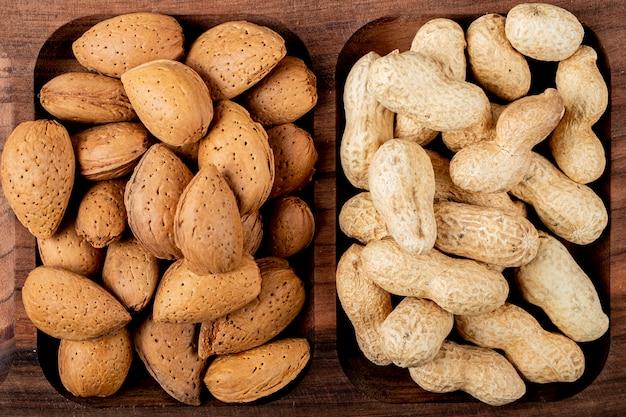 Vista superiore delle mandorle matte con le arachidi nelle coperture su un vassoio di legno
