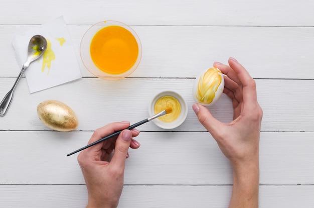 Vista superiore delle mani che dipingono uovo per pasqua