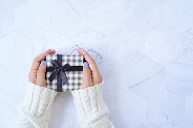 Vista superiore delle mani che tengono il contenitore di regalo dalla celebrazione o dal regalo di natale del nuovo anno su fondo di marmo bianco, concetto di festa