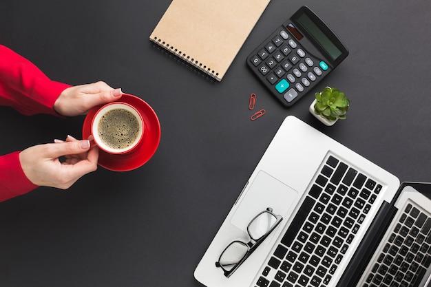 Vista superiore delle mani che tengono la tazza di caffè sullo scrittorio del lavoro
