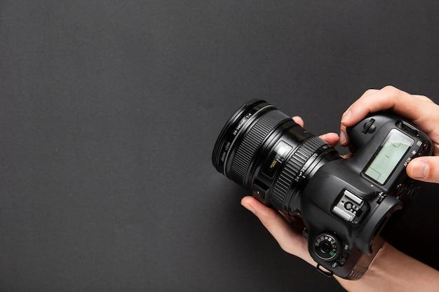 Vista superiore delle mani che tengono una macchina fotografica con lo spazio della copia