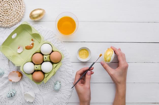 Vista superiore delle mani che tingono uovo per pasqua