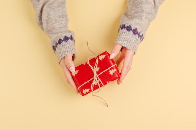 Vista superiore delle mani della donna che tengono il contenitore di regalo