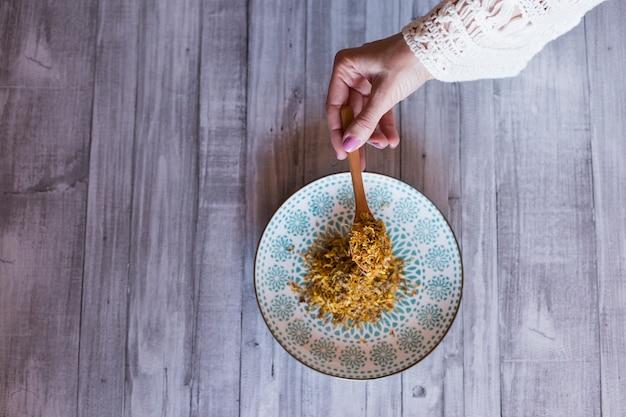 Vista superiore delle mani della donna che tengono un cucchiaio con curcuma gialla. tavolo in legno grigio sfondo. concetto di stile di vita diurno e sano