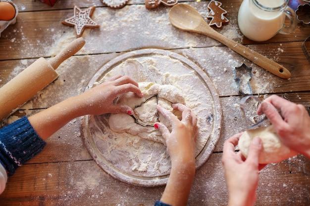 Vista superiore delle mani della madre e del bambino che producono i biscotti dell'albero di natale.