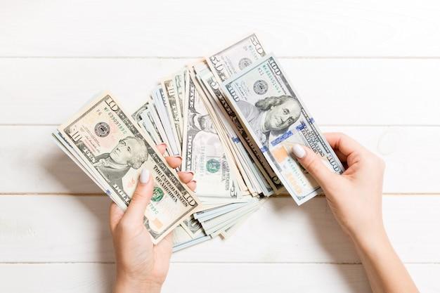 Vista superiore delle mani femminili che contano soldi. cento altre banconote in dollari sulla parete di legno. concetto di affari