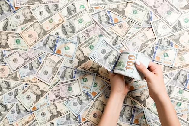 Vista superiore delle mani femminili che contano soldi sui dollari