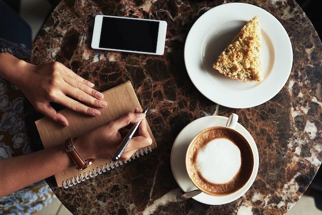 Vista superiore delle mani femminili che fanno le note ad una pausa del dessert e del caffè