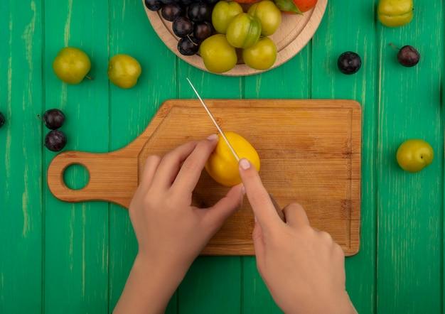 Vista superiore delle mani femminili che tagliano la pesca gialla con il coltello su una tavola di legno della cucina su un fondo di legno verde