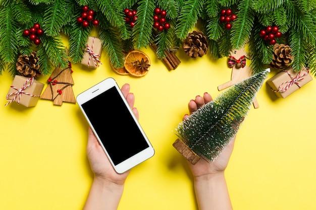 Vista superiore delle mani femminili che tengono il telefono in una mano e l'albero di natale in un'altra mano. concetto di vacanza di capodanno. modello