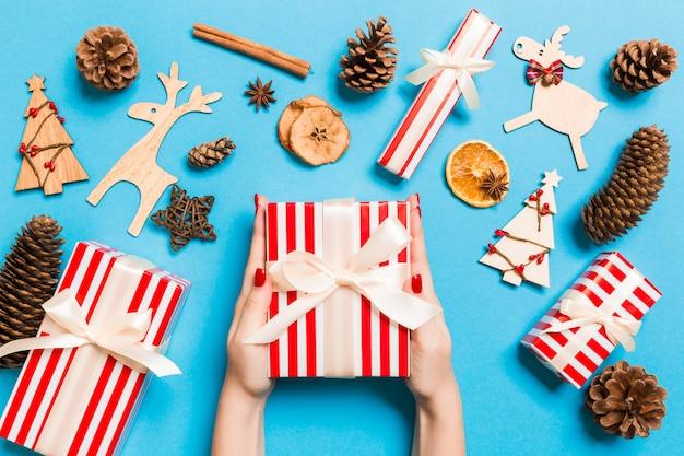 Vista superiore delle mani femminili che tengono un regalo di natale su fondo blu festivo