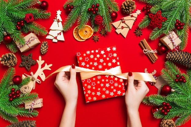 Vista superiore delle mani femminili che tengono un regalo di natale su fondo rosso festivo