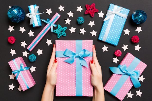 Vista superiore delle mani femminili che tengono un regalo di natale sul nero festivo.