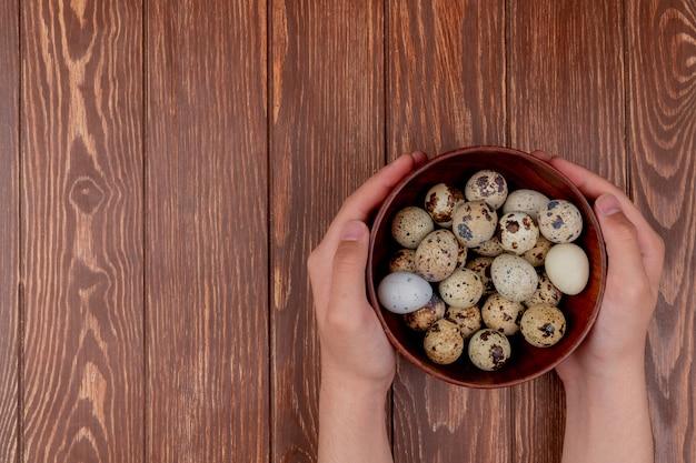 Vista superiore delle mani femminili che tengono una ciotola di legno di uova di quaglia su un fondo di legno con lo spazio della copia
