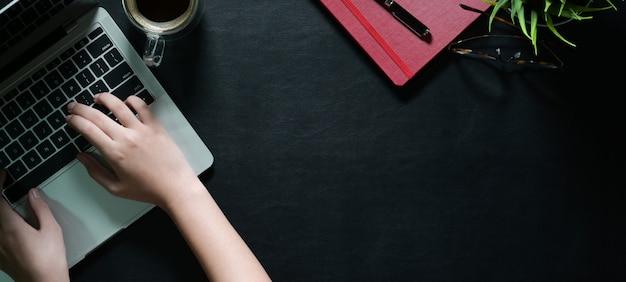 Vista superiore delle mani femminili con il computer portatile che scrive sullo scrittorio di cuoio scuro e sullo spazio della copia