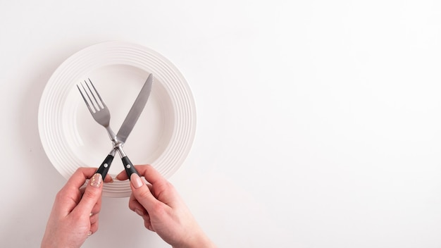 Vista superiore delle mani femminili con la forchetta, il coltello e il piatto vuoto su bianco