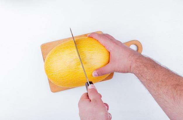 Vista superiore delle mani maschii che tagliano melone con il coltello sul tagliere su fondo bianco
